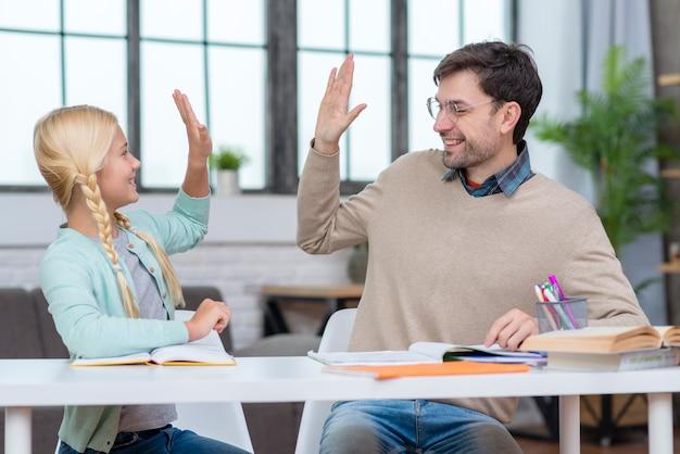 Leraar en jonge student high five