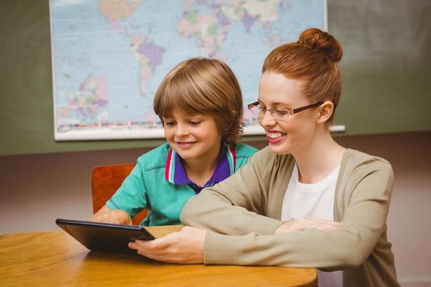 Leraar en jongen die digitale tablet in klaslokaal gebruiken