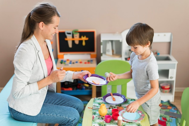Leraar en kind spelen samen