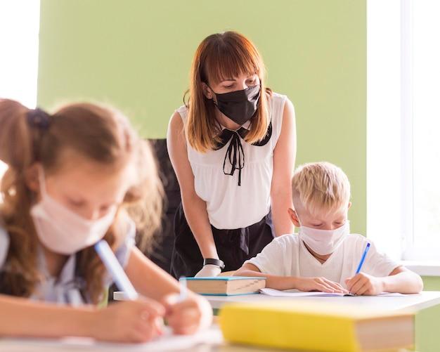 Leraar en kinderen beschermen zichzelf met gezichtsmaskers in de klas