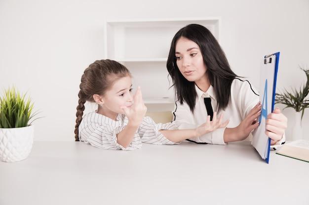 Leraar en klein meisje werken samen aan een uitspraak in de klas.