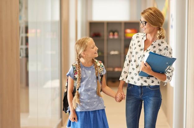 Leraar en kleine student op weg naar klaslokaal