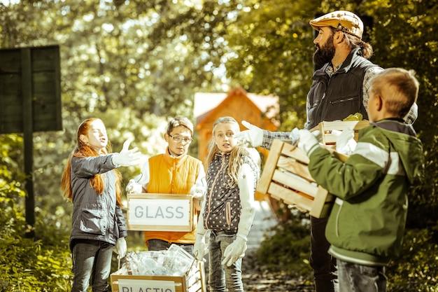 Leraar en leerling praten bij het sorteren van afval in het bos op een mooie dag