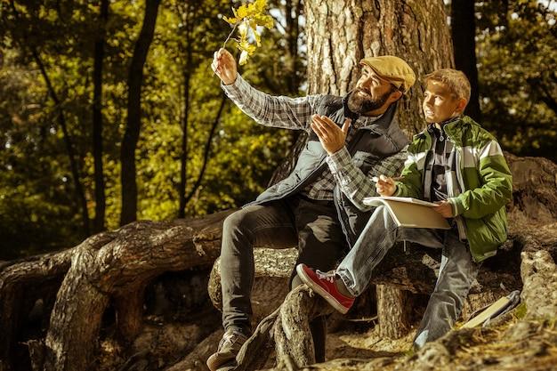 Leraar en student met een les ecologie in park op een zonnige dag