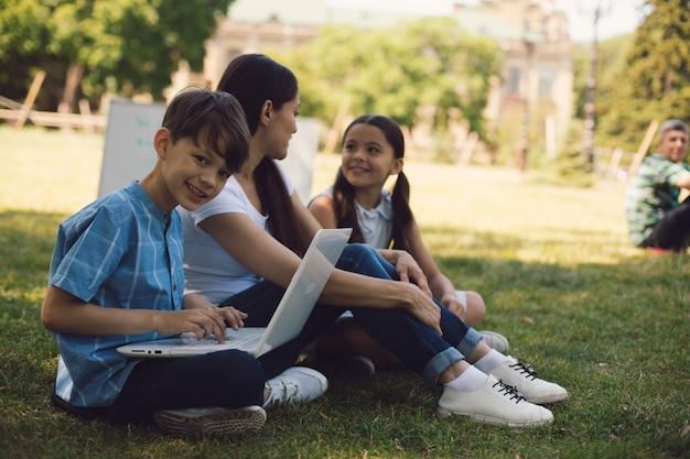 Leraar en twee jonge studenten gebruiken laptop in park