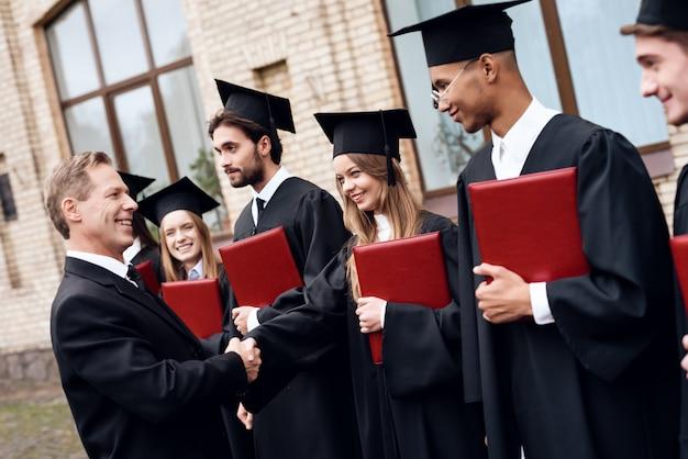 Leraar geeft de studentendiploma's op de binnenplaats van de universiteit