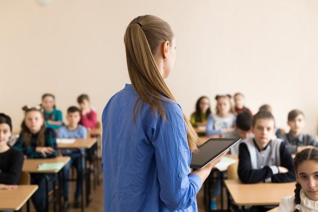 Leraar haar studenten een vraag stellen op de basisschool met tabletcomputer