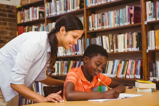 Leraar helpende jongen met thuiswerk in bibliotheek