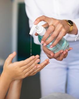 Leraar helpt een kind zijn handen te desinfecteren