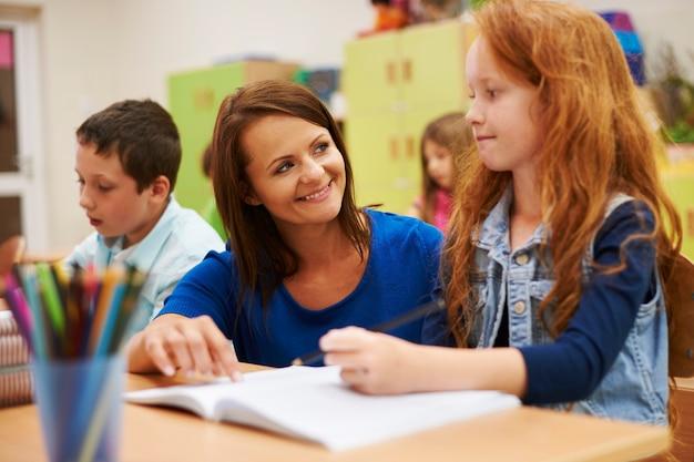 Leraar helpt haar schattige leerling