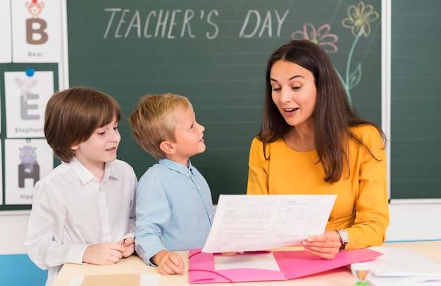 Leraar helpt haar studenten in de klas