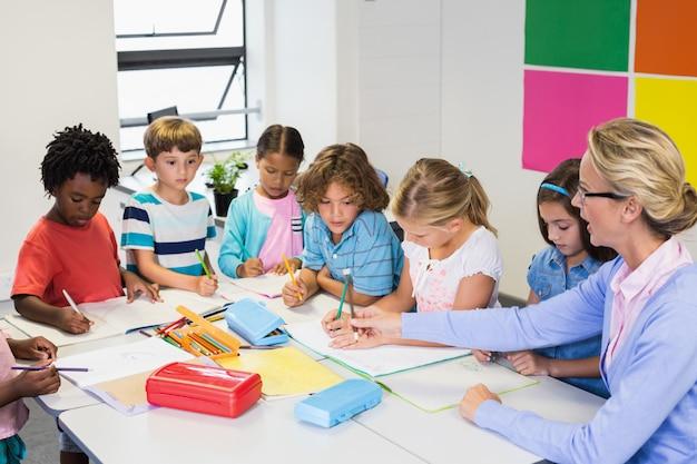 Leraar helpt kinderen met hun huiswerk in de klas
