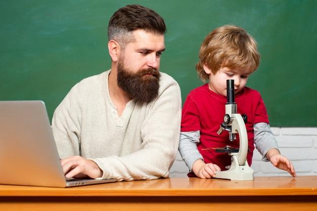 Leraar helpt leerlingen studeren op bureaus in de klas jonge jongen doet zijn school huiswerk met zijn f...