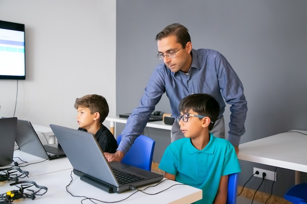 Leraar in glazen die achter leerling staan en taak op laptop controleren