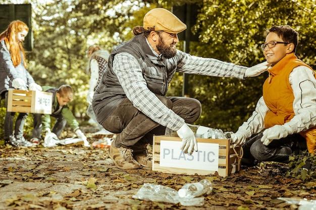 Leraar juicht zijn leerling toe voor het sorteren van plastic in dozen in het bos op een mooie dag