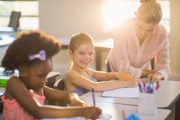 Leraar kinderen helpen met hun huiswerk in de klas