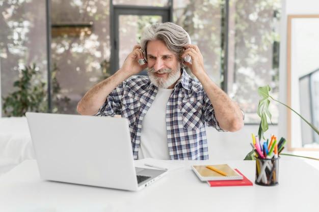 Leraar koptelefoon zetten op bureau