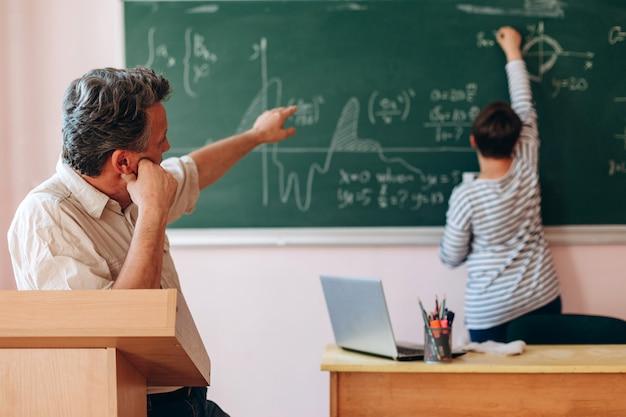 Leraar legt een les uit aan een student die naast een schoolbord staat.