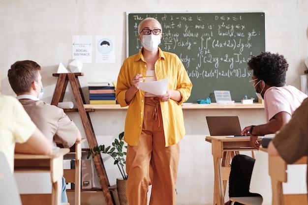Leraar lesgeven aan studenten op school tijdens pandemie
