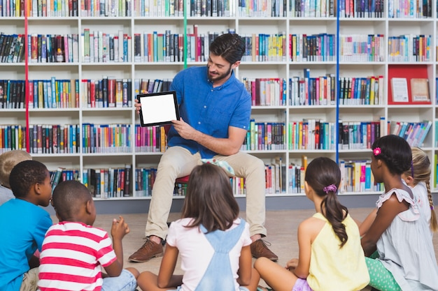 Leraar lesgeven kinderen op digitale tablet in bibliotheek
