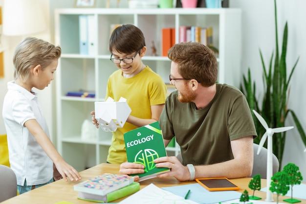 Leraar luistert aandachtig. glimlachende donkerharige jongen die plastic huis inspecteert tijdens de les en plezier heeft met klasgenoot