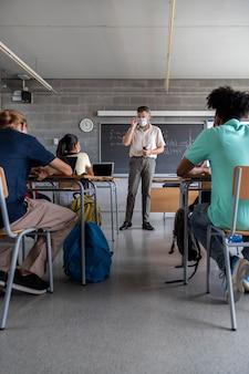 Leraar met gezichtsmasker multiraciale tiener middelbare scholieren luisteren naar les