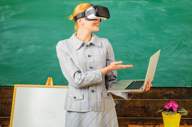 Leraar met laptop in vr-headset. moderne technologieën in slimme school. digitaal onderwijs. lachende tutor in de klas.