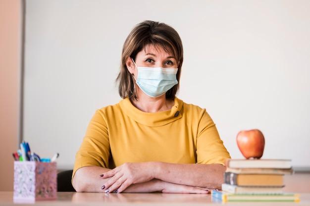 Leraar met masker bij bureau