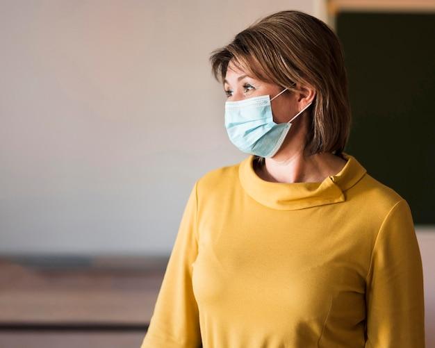 Leraar met masker in de klas