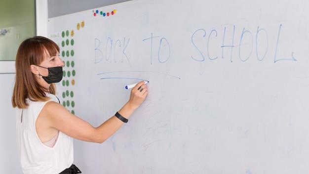 Leraar met medisch masker dat op het whiteboard schrijft