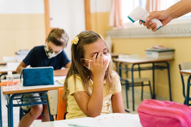 Leraar neemt de temperatuur van een meisje in de klas met een thermometer tijdens de covid-pandemie. ze is ziek en heeft koorts, ze heeft de covidziekte.