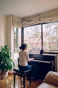 Leraar pianist musicus die klassieke muziek repeteert. professionele muzikantenlevensstijlen binnenshuis. jonge donkerbruine vrouw die de piano thuis speelt. geïsoleerde vrouwenpianist die een nieuw klassiek lied samenstelt.
