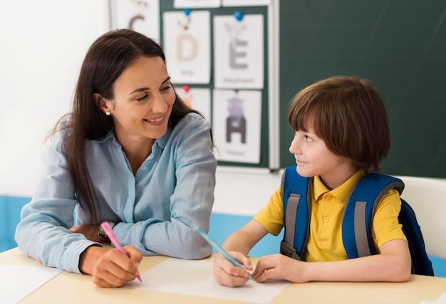 Leraar praat met haar student in de klas