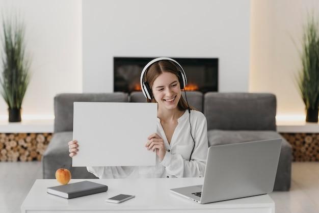 Leraar praat met haar studenten online en houdt een groot papier vast