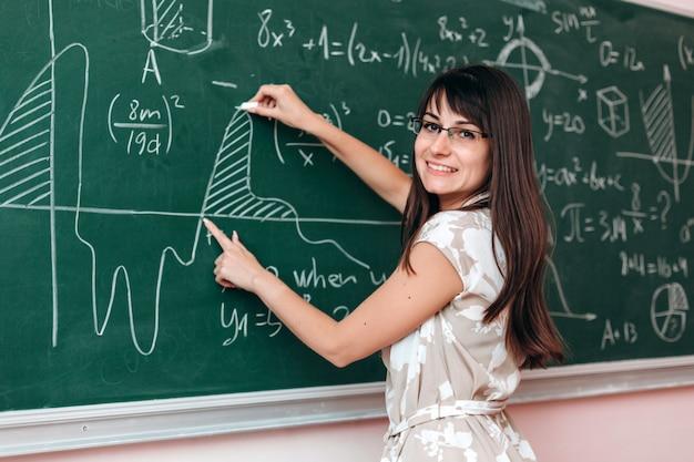 Leraar schrijft een voorbeeld op het bord en legt een les uit die naar de camera kijkt.