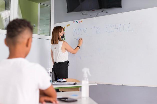 Leraar schrijft iets op het whiteboard met kopie ruimte