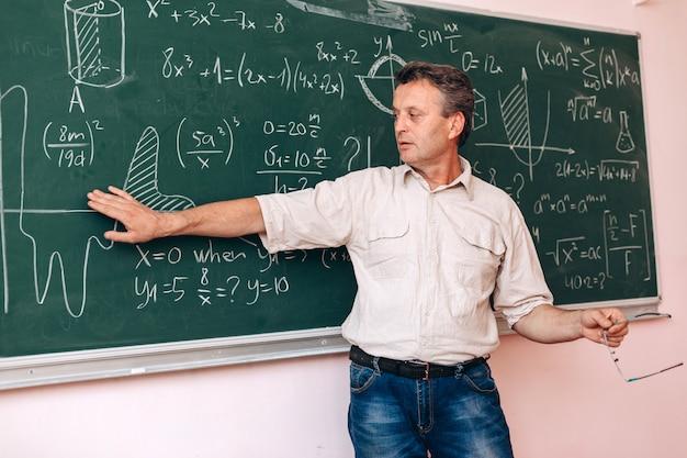Leraar schrijft op het bord en legt een les uit.