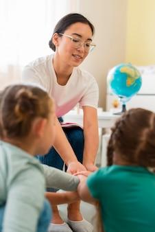 Leraar speelt met haar leerlingen op de kleuterschool
