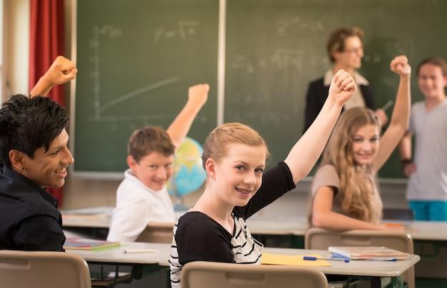 Leraar staat tijdens de les voor een schoolbord en geeft les of geeft les aan studenten, die informeren en leren in de klas
