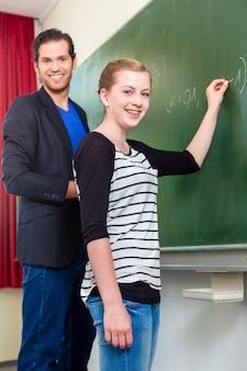 Leraar testen tijdens lessen studenten of meisje op school voor de klas op het bord of bord of bord in wiskunde