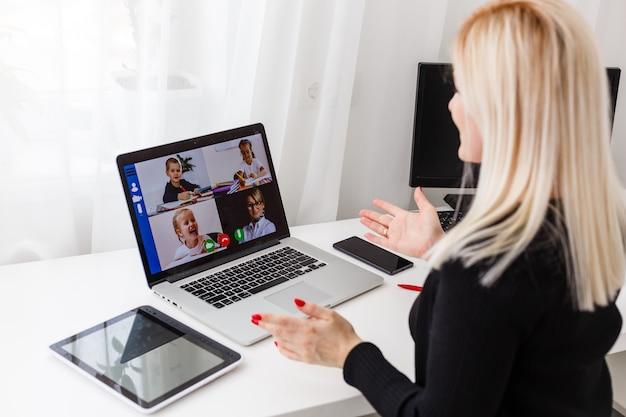 Leraar, tutor of professor met headset, laptop en camera in haar kantoor die iets uitlegt tijdens een online les of videocollege, webinar