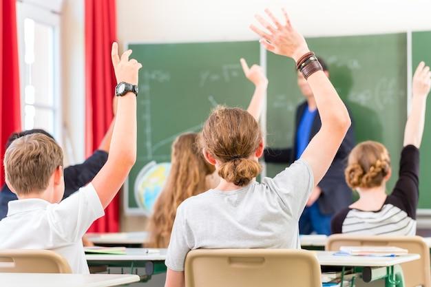 Leraar van de klas geeft les voor een schoolbord of bord en onderwijst studenten of leerlingen, ze steken hun hand op omdat ze alle antwoorden kennen