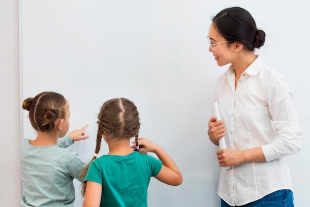 Leraar vertelt haar studenten wat ze op een wit bord moeten schrijven