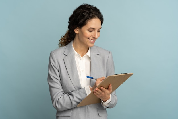 Leraar vrouw draagt grijze blazer schrijven, maakt aantekeningen in document, houdt map in haar hand geïsoleerd