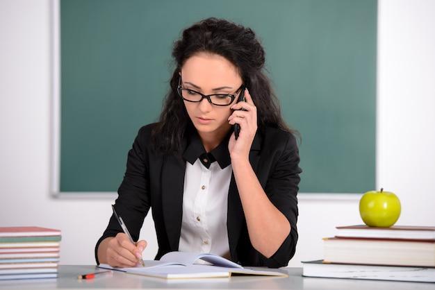 Leraar zit aan de tafel en praat aan de telefoon.