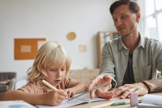 Leraar zit aan tafel met zijn leerling en legt hem het nieuwe onderwerp uit