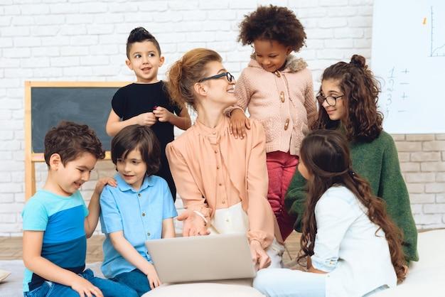 Leraar zit met schoolkinderen die haar hebben omringd.