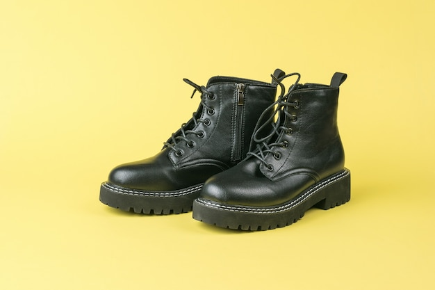 Leren brute schoenen met hoge zolen met veters op een gele ondergrond
