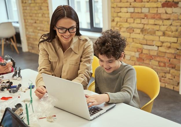 Leren coderen van lachende jonge vrouwelijke leraar met een bril die wetenschappelijke robotica-video laat zien aan