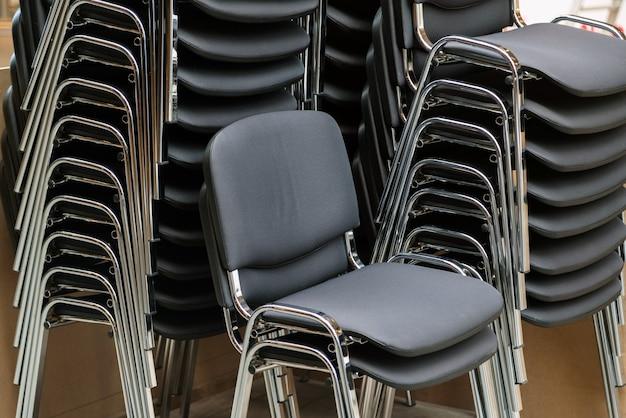 Leren en metalen stoelen op elkaar gestapeld in de vergaderruimte.
